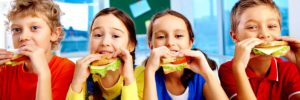 Kids eating sandwiches, school lunch program